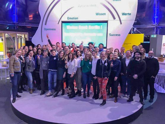 Das EY ALTER Team steht auf einer Bühne in der Ausstellung im Gasometer Berlin.